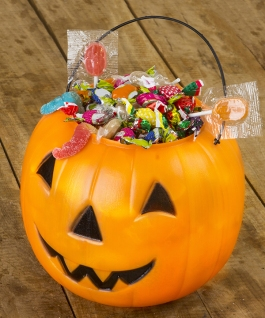 Halloween plastic pumpkin filled with candy on wooden table